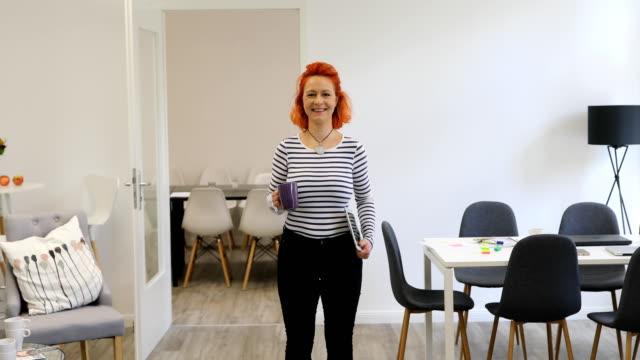 stockvideo's en b-roll-footage met glimlachende zakenvrouw met koffiemok en laptop - alleen oudere vrouwen