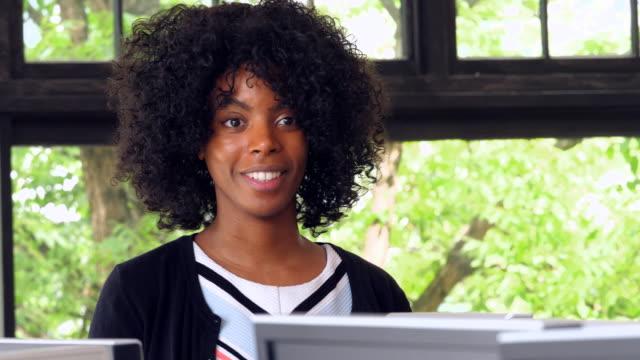 ms smiling businesswoman working at computer in high tech office - solo una donna di età media video stock e b–roll