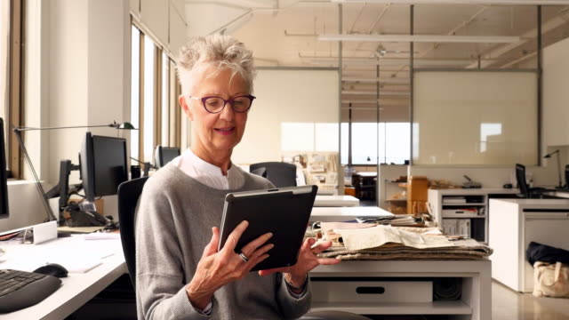vídeos de stock e filmes b-roll de ms zi smiling businesswoman working on digital tablet at office workstation - só uma mulher idosa