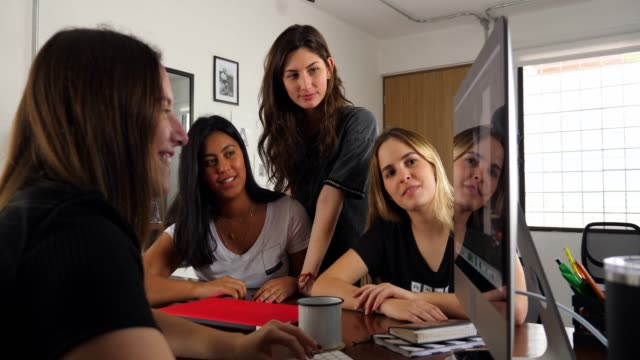 vidéos et rushes de ms smiling businesswomen having project meeting at computer in design office - agence de design