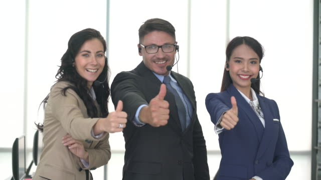smiling call center business team making thumbs up gesture - thumbs up stock videos & royalty-free footage