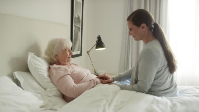 vídeos y material grabado en eventos de stock de cuidador sonriente que se aferra al paciente de edad avanzada - proceso de envejecimiento
