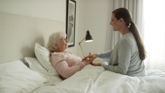 vídeos y material grabado en eventos de stock de cuidador sonriente hablando con pacientes de edad avanzada - asistente sanitario