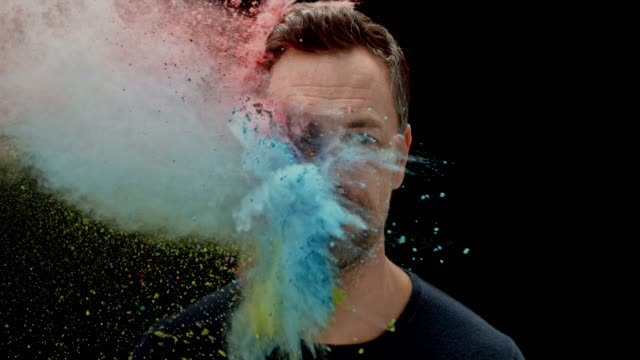 vídeos de stock e filmes b-roll de slo mo smiling caucasian man being hit with a multi colored powder - olhos fechados