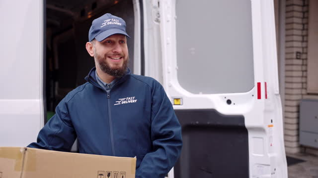 smiling caucasian mature gig delivery driver holding package and standing in front of a van - van stock videos & royalty-free footage