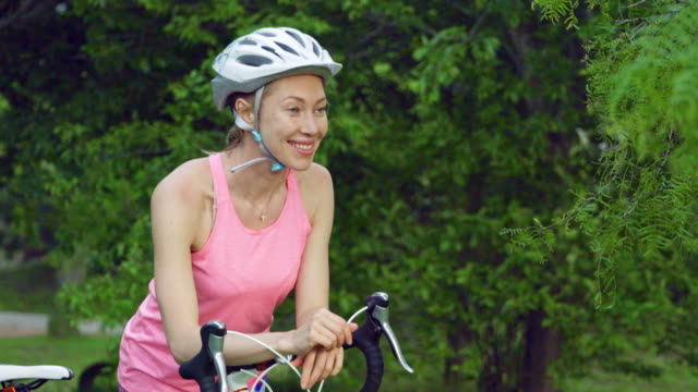 smiling caucasian woman in cycling attire resting on her bicycle - sports helmet stock videos & royalty-free footage