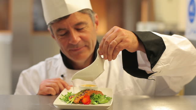 smiling chef pouring dressing over salmon dish - condiments stock videos and b-roll footage