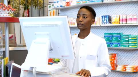 vidéos et rushes de chimiste souriant à l'aide d'ordinateur à pharmacie - cadrage à la taille