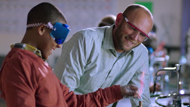 vidéos et rushes de a smiling chemistry teacher engages with a student during a lab experiment. - montrer la voie