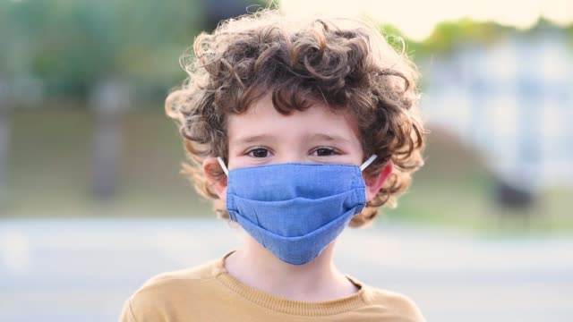smiling child behind the normal new coronavirus / covid-19 protection mask - protezione video stock e b–roll