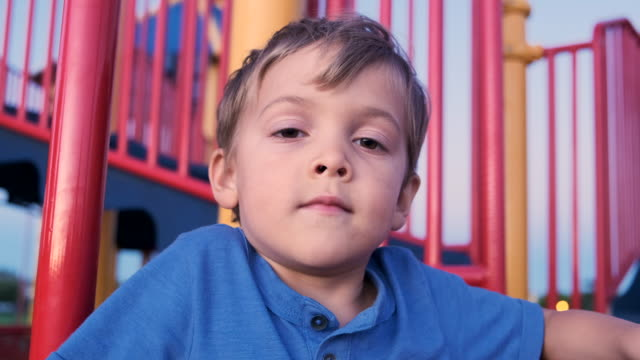 smiling child boy looking at the camera at the playground - smirking stock videos and b-roll footage