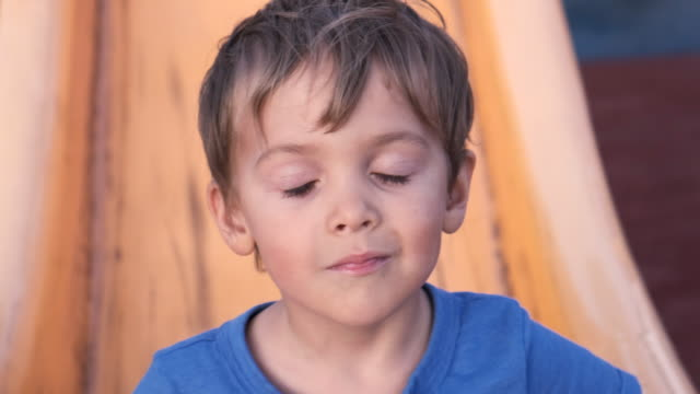 smiling child boy looking at the camera sitting in a playground slide - toddler stock videos & royalty-free footage
