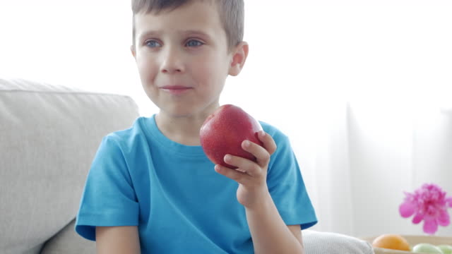 Smiling child eating a red apple in the living room