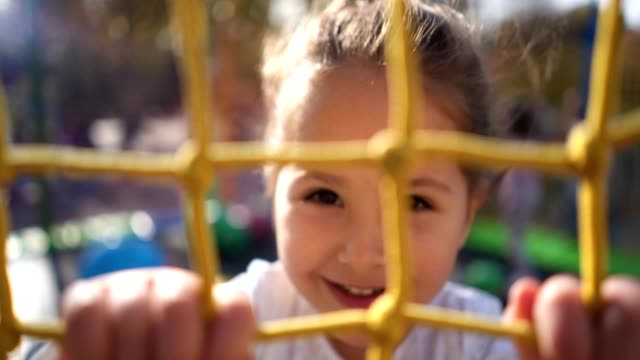 smiling child enjoying jumping on a trampoline on a playground - non us film location stock videos & royalty-free footage