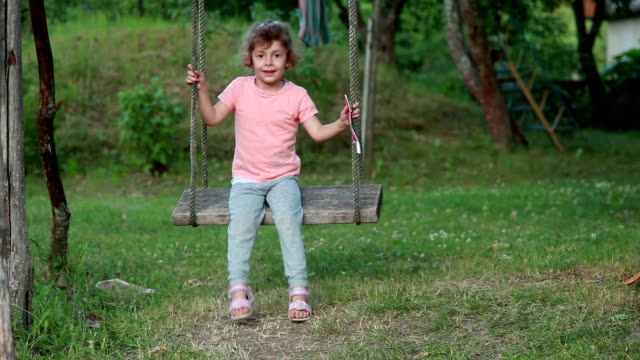 smiling child swinging on a rope swing in the backyard - rope swing stock videos & royalty-free footage