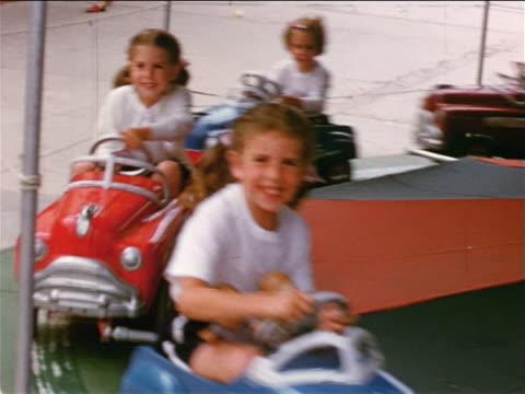 1951/52 HOME MOVIE smiling children riding car merry-go-round at amusement park