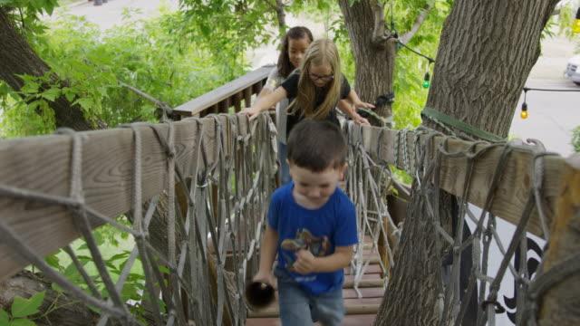 Smiling children running on tree bridge / Provo, Utah, United States