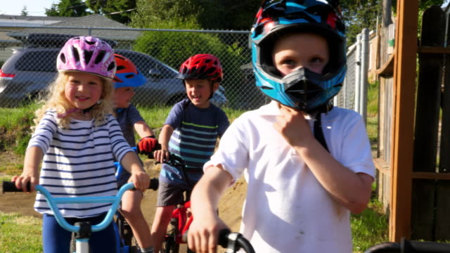 pan r/f smiling children sitting on bmx bikes waiting to ride on backyard dirt track on summer afternoon - cycling helmet stock videos & royalty-free footage