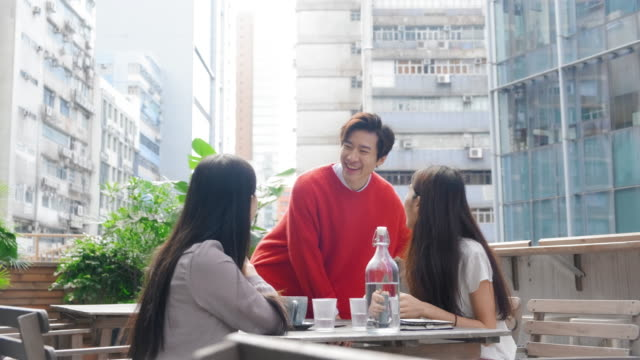 smiling chinese man joining friends on outdoor terrace - male with group of females stock videos & royalty-free footage