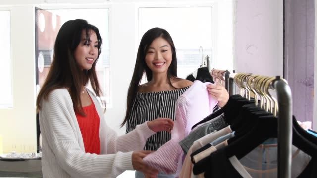 smiling chinese women shopping for clothes in fashion store - clothes shop stock videos & royalty-free footage