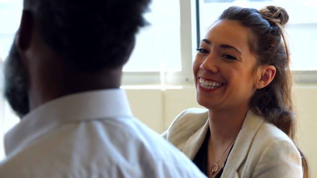 cu smiling colleagues in discussion during meeting in tech office - colleague stock videos & royalty-free footage