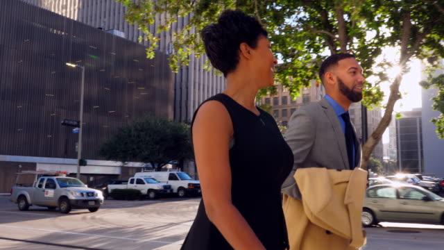 vidéos et rushes de ts smiling colleagues in discussion while walking on city sidewalk - jour