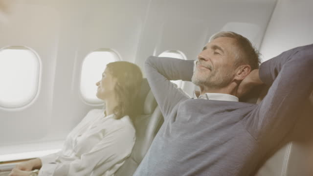 smiling colleagues relaxing in corporate jet - comfortable stock videos & royalty-free footage