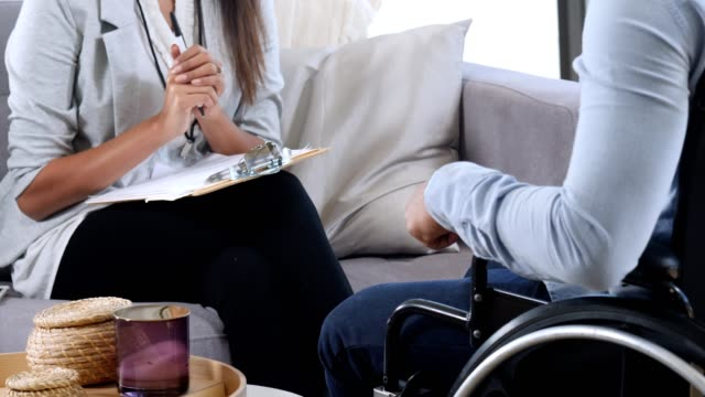 smiling counselor talks with a man in wheelchair - solutions stock videos & royalty-free footage