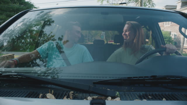 stockvideo's en b-roll-footage met smiling couple drive down street in car, close up - voorruit