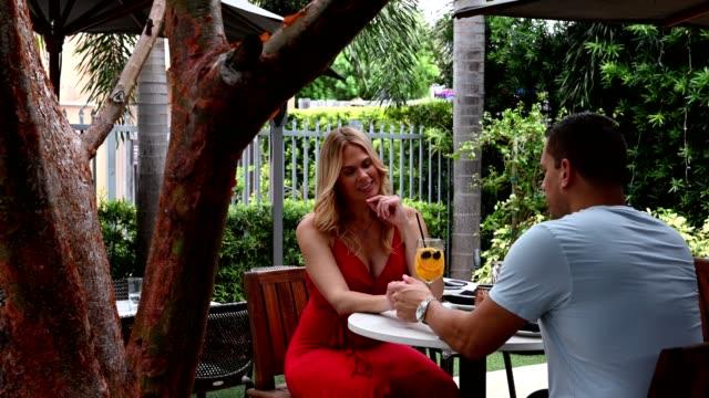 leende par håller händerna på restaurang - tre fjärdedels längd bildbanksvideor och videomaterial från bakom kulisserna
