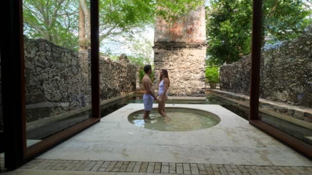 vídeos y material grabado en eventos de stock de zi smiling couple holding hands in outdoor bath at luxury resort - lugar turístico