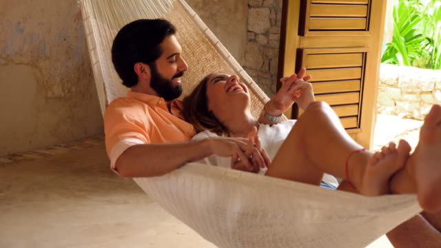 MS Smiling couple holding hands while relaxing in hammock in room at luxury resort