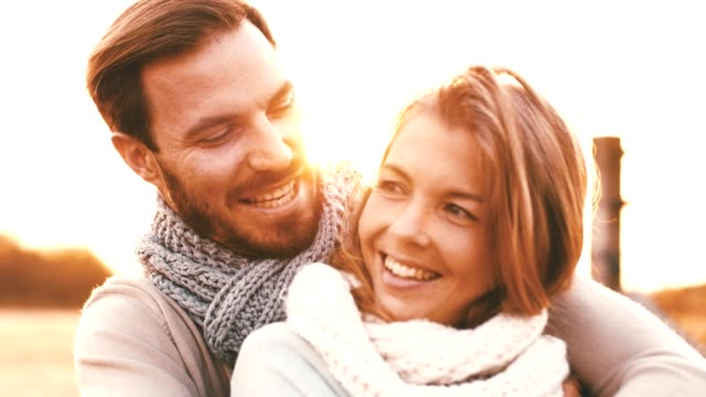 smiling couple hugging outdoors at sunny day - heterosexual couple stock videos & royalty-free footage