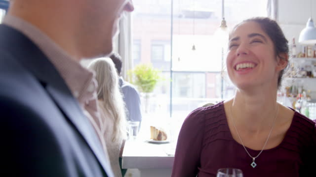 MS smiling couple in discussion in restaurant bar drinking wine