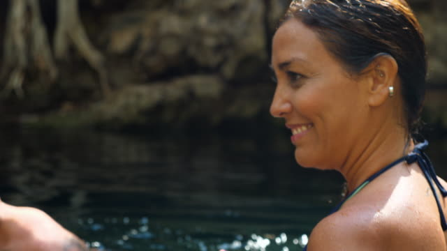 cu smiling couple in discussion while swimming together in cenote - real wife sharing stock-videos und b-roll-filmmaterial