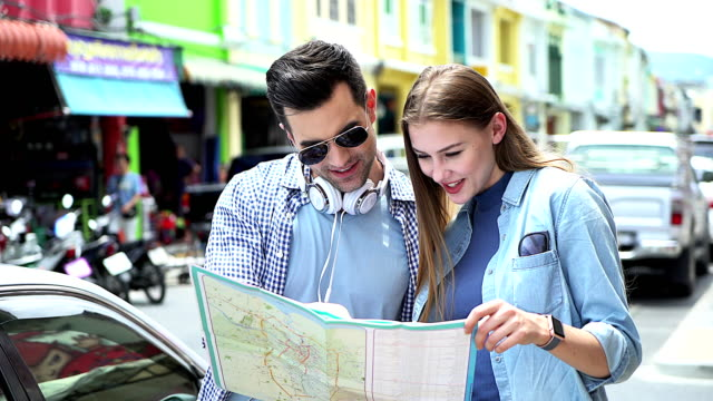 smiling couple in sunglasses with map in the city summer holidays, dating and tourism concept. - zaino da montagna video stock e b–roll