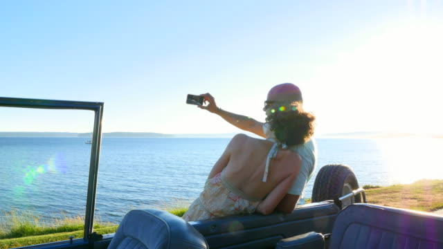 stockvideo's en b-roll-footage met ms pan smiling couple leaning on convertible parked along waterfront taking self portrait with smartphone - mid volwassen koppel