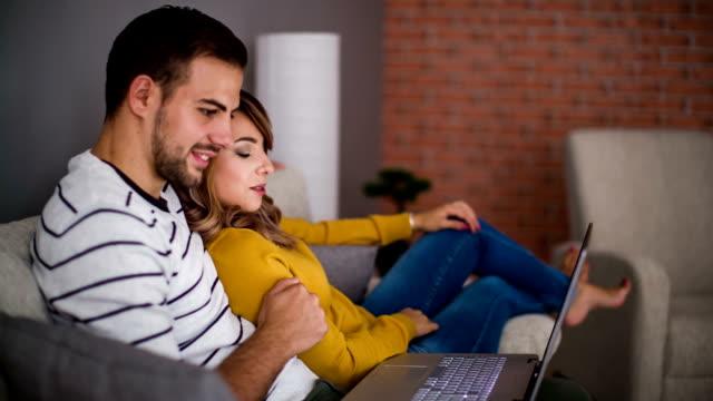 vídeos de stock e filmes b-roll de sorridente casal olhando para laptop - confortável