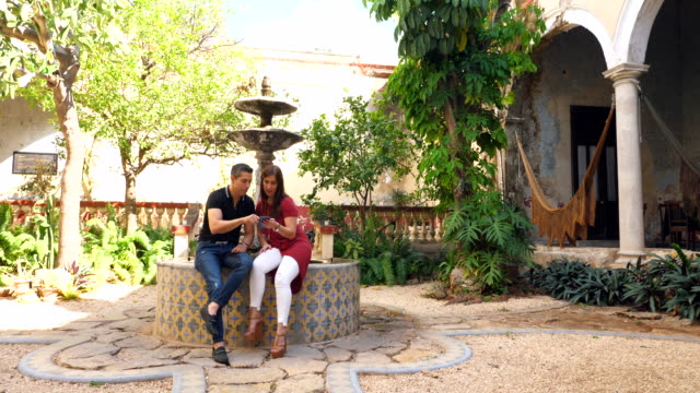 ms smiling couple looking at smart phone while touring courtyard of villa - real wife sharing stock-videos und b-roll-filmmaterial