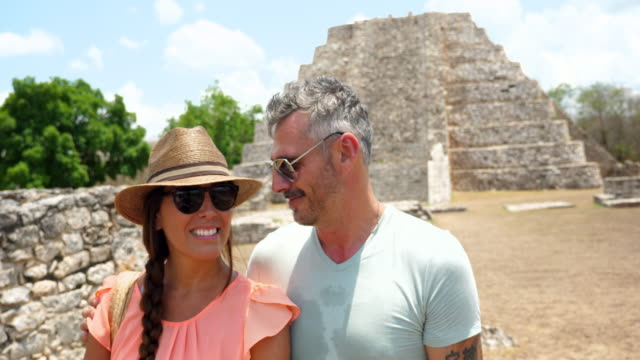 ms smiling couple posing for photo in front of mayapan ruins while on vacation - yucatan peninsula stock videos and b-roll footage