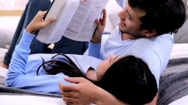 夫婦一緒にベッドで本を読んでは笑ってください。hd フォーマット。 - ヘッドボード点の映像素材/bロール