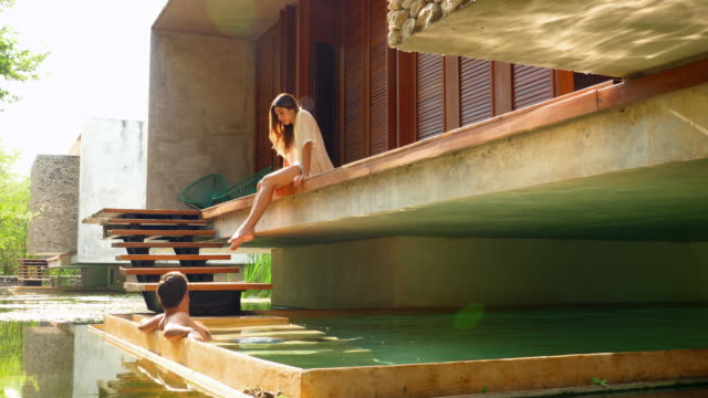 vidéos et rushes de ms smiling couple relaxing by plunge pool outside of bungalow at luxury tropical resort - dimanche