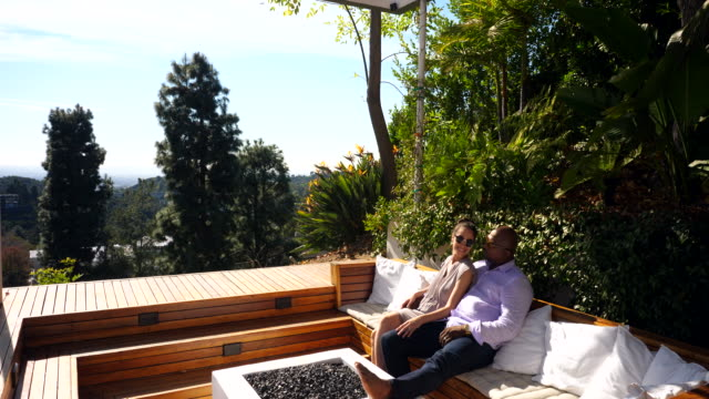 ms smiling couple relaxing on outdoor furniture on sunny afternoon - sunny video stock e b–roll