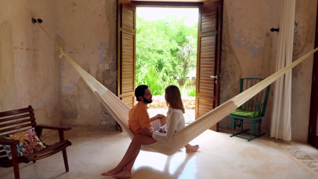 ms smiling couple relaxing together in hammock in room at luxury resort - 20 29 years stock videos & royalty-free footage