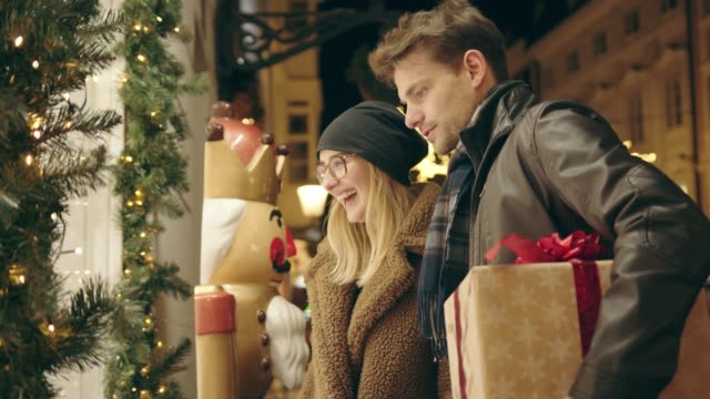 smiling couple shopping for christmas gifts, looking at the front of a gift shop - christmas market stock videos & royalty-free footage