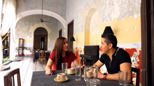ms smiling couple sitting at cafe table in courtyard of villa - real wife sharing stock-videos und b-roll-filmmaterial