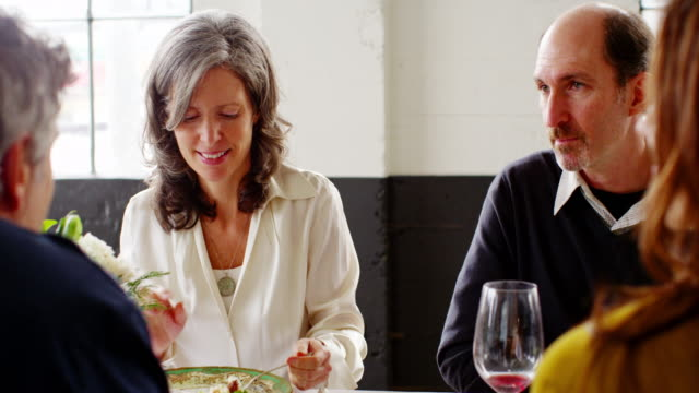ms smiling couple sitting at dinner party with friends in loft eating dinner - dinner party stock videos & royalty-free footage