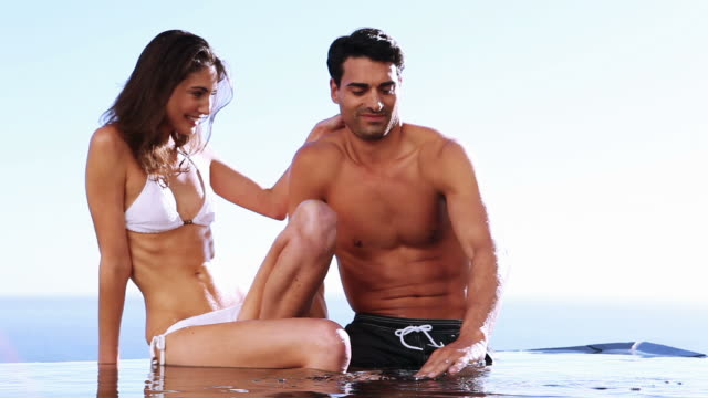 smiling couple sitting in a swimming pool - braunes haar stock-videos und b-roll-filmmaterial