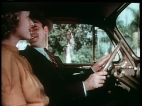 stockvideo's en b-roll-footage met 1940 smiling couple sitting in car - passagiersstoel