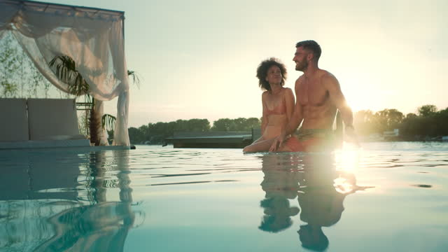 smiling couple sitting on the pool side and talking. - standing water stock videos & royalty-free footage